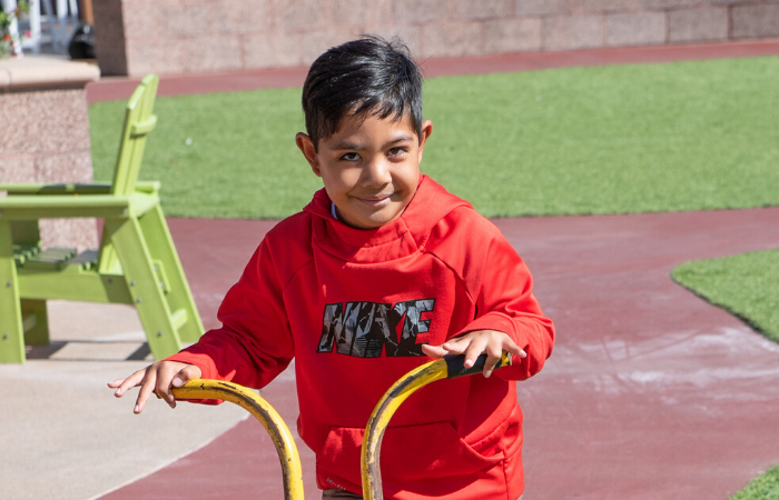 Boy rides scooter around outdoor trike trail.
